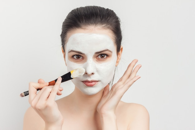 Portrait young beautiful woman applying a face mask with a brush