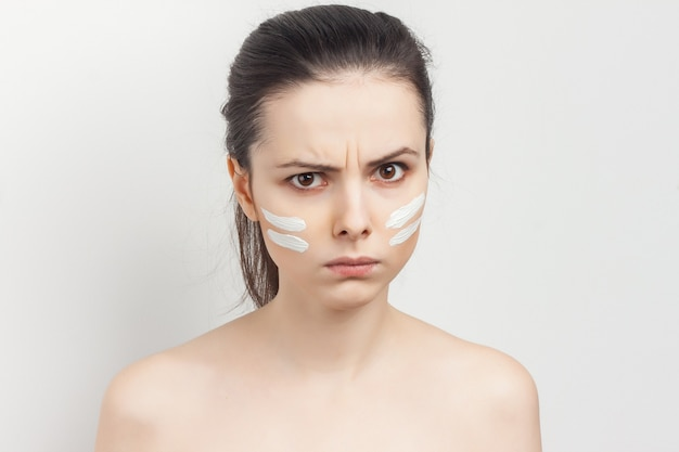 Portrait young beautiful woman applying a face mask