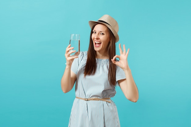 Portrait of young beautiful woman in blue dress, hat holding and drinking clear fresh pure water from glass isolated on blue background. healthy lifestyle, people sincere emotions concept. copy space.