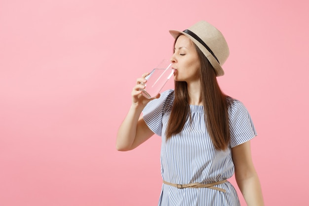 Portrait of young beautiful woman in blue dress, hat holding and drinking clear fresh pure water from glass isolated on pink background. healthy lifestyle, people, sincere emotions concept. copy space