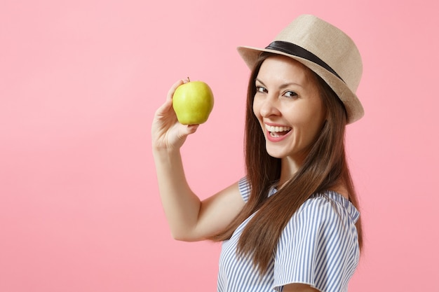 Portrait of young beautiful woman in blue dress, summer straw hat holding, eating green fresh apple fruit isolated on pink background. healthy lifestyle, people, sincere emotions concept. copy space.