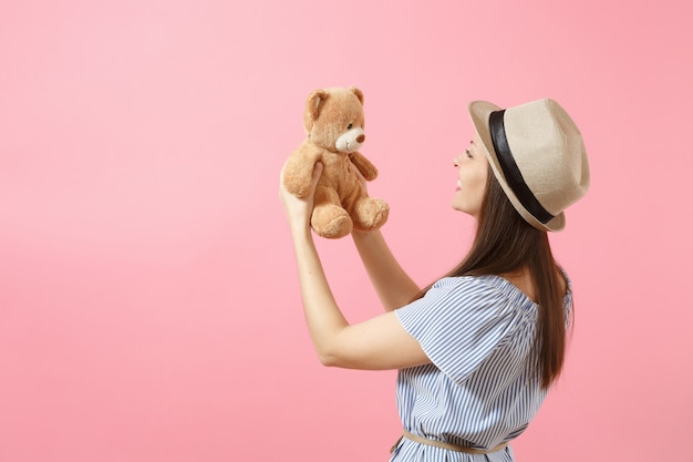 Portrait of young beautiful woman in blue dress, summer straw hat holding teddy bear plush toy isolated on pink background. people, sincere emotions, lifestyle concept. advertising area. copy space.