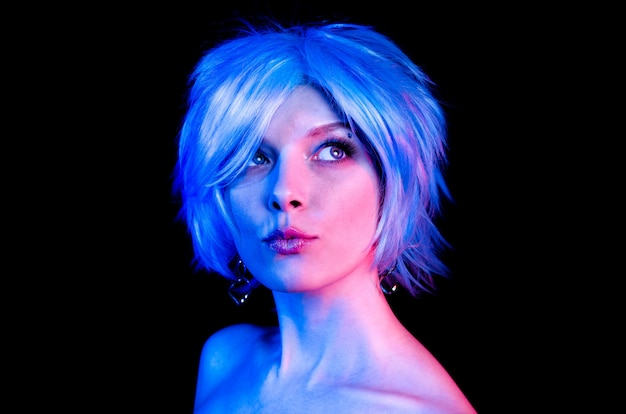 Portrait of young beautiful woman in blue wig
