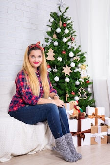 Portrait of young beautiful woman in decorated room with christmas tree