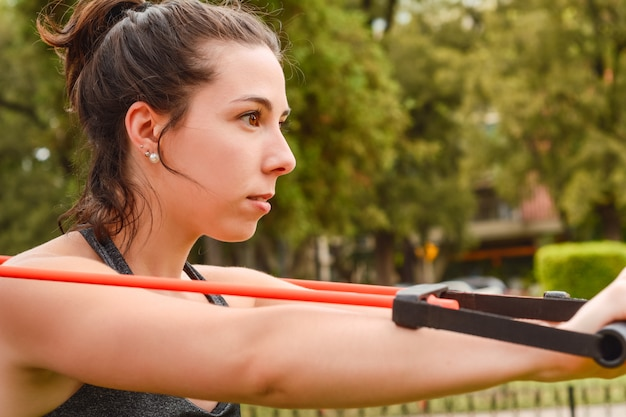 Portrait of young beautiful woman doing exercise at park