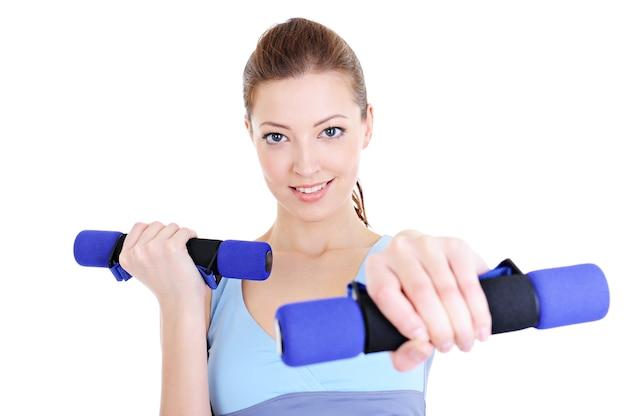 Ritratto di giovane donna bellissima facendo esercizi fisici con manubri