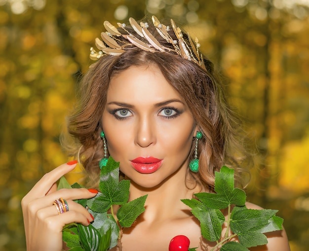 Portrait of a young beautiful woman in a dress made of autumn leaves in the park in autumn season with bouquet of flowers in her hands. art photo