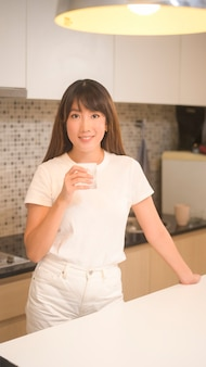 A portrait of young beautiful woman drinking glass of water in kitchen