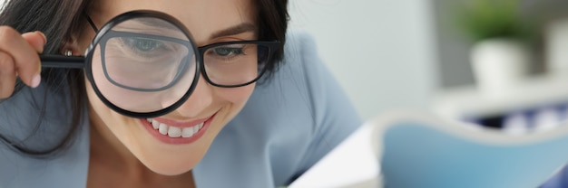 Portrait of young beautiful woman examining documents through magnifying glass