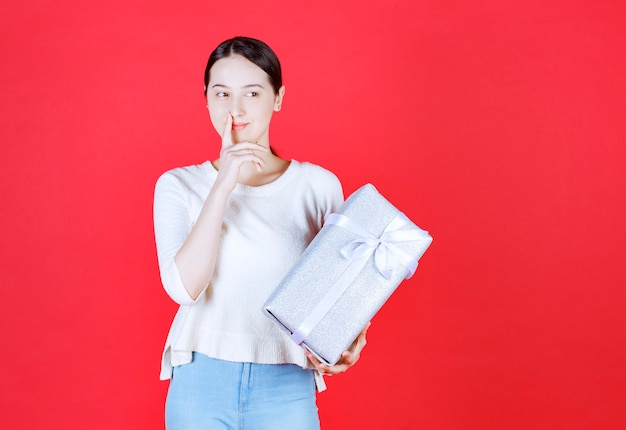 Portrait of young beautiful woman holding gift box and thinking