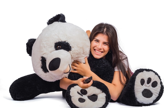 Ritratto di giovane bella donna che abbraccia un grande orsacchiotto isolato su studio.