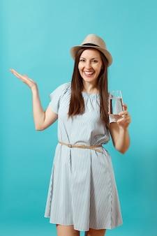 파란 드레스를 입은 아름다운 젊은 여성의 초상화, 파란 배경에 격리된 맑고 깨끗한 물 한 잔을 들고 있는 모자. 건강한 생활 방식, 사람들은 진실한 감정 개념입니다. 복사 공간에 손을 가리키는.