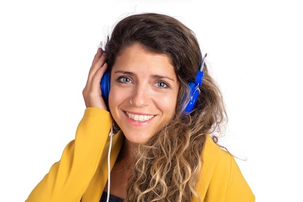 Ritratto di giovane bella donna che ascolta la musica con le cuffie blu