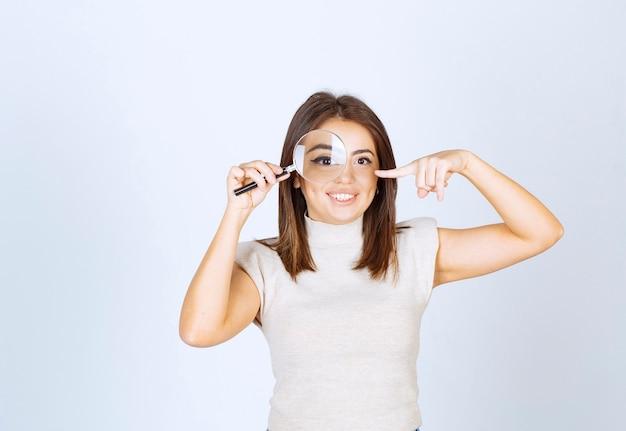 Ritratto di giovane bella donna che guarda tramite una lente d'ingrandimento isolata sopra fondo bianco.