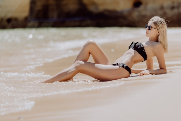 Portrait of a young beautiful woman lying on sand at ocean beach