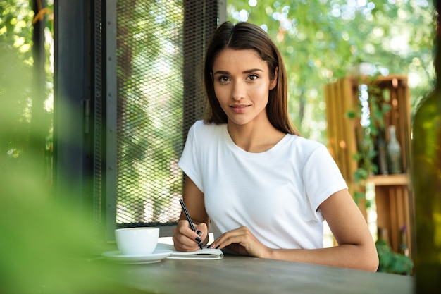 Portrait of a young beautiful woman making notes in a textbook
