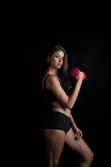 Portrait of young beautiful woman making physical exercises with dumbbells