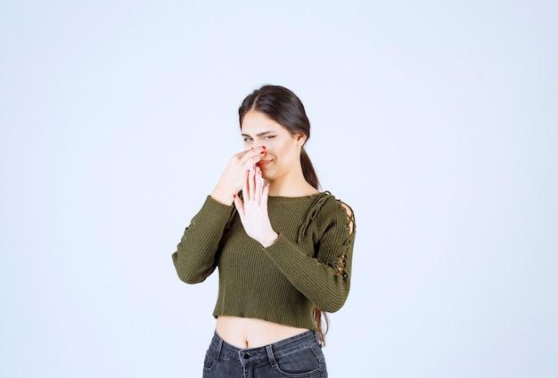Ritratto di un modello di giovane bella donna che tiene il naso a causa dell'odore