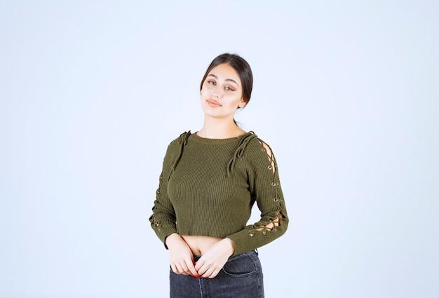 Ritratto di un modello di giovane bella donna in piedi e in posa sul muro bianco.