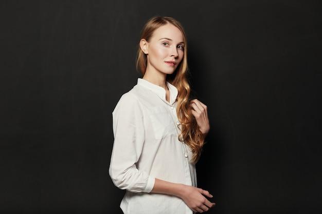 Портрет молодой, красивой женщины на черном фоне