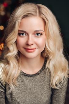 Il ritratto di giovane bella donna posa per la macchina fotografica e sorride