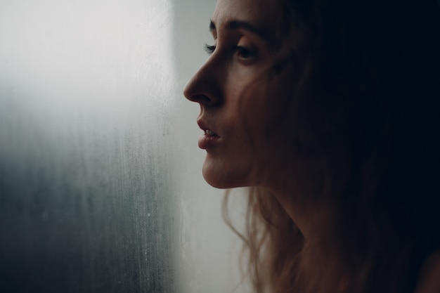 Portrait of young beautiful woman in profile near misted window