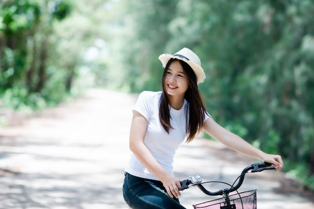 Portrait of young beautiful woman riding a bicycle in a park.