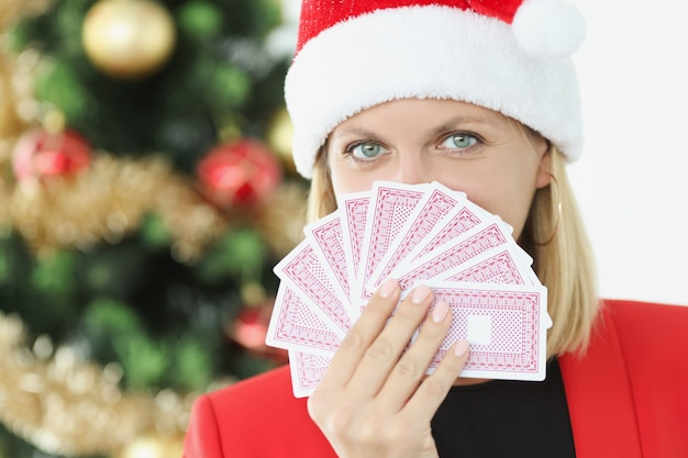 Portrait of young beautiful woman in santa claus hat holding playing cards on background of new