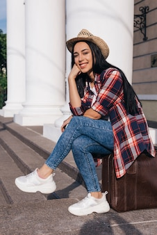 Portrait of young beautiful woman sitting on luggage bag looking at camera