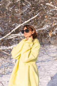 Portrait of a young beautiful woman in a snowy landscape winter forest on a sunny day, dressed in a yellow big pullover, with sunglasses, enjoying the sun and snow