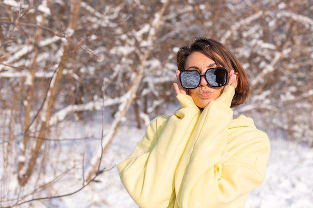 Ritratto di una giovane bella donna in una foresta di inverno paesaggio innevato in una giornata di sole, vestita con un grande pullover giallo, con occhiali da sole, godersi il sole e la neve