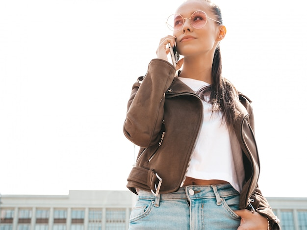 Portrait of young beautiful woman speaking on phone  trendy girl in casual summer clothes  serious female posing on the street