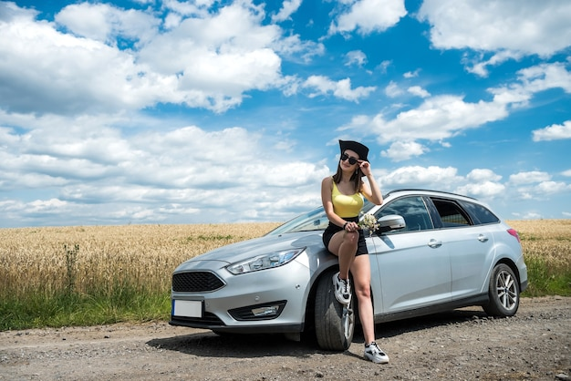 Portrait of young beautiful woman standing near her car at rural road. dream for perfect trip in summer time