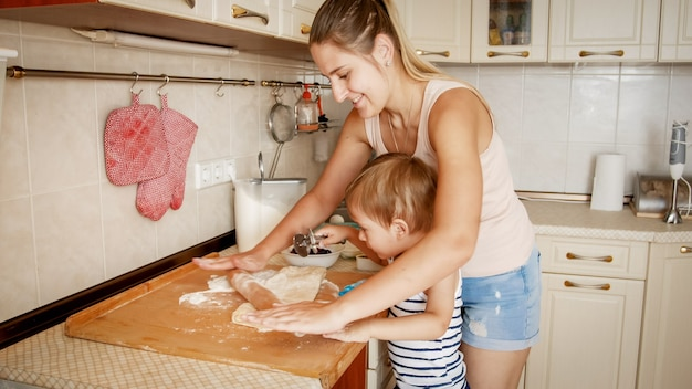 Portrait of young beautiful woman teaching her little child boy making cookies and baking pies on kitchen at home