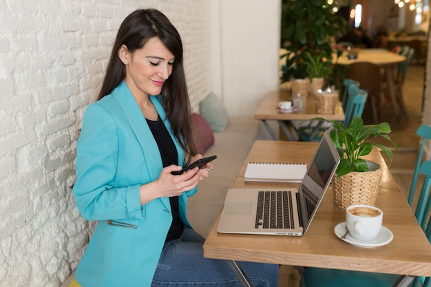 Portrait of a young beautiful woman using mobile phone in a restaurant. she is smiling. modern life of a blogger with computer laptop, tablet, notebook and coffee on table. casual clothes. lifestyle