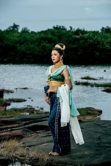 Портрет молодой красивой женщины в традиционном костюме с орнаментом, позирующей на природе в таиланде