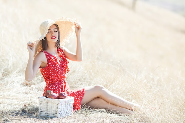 Portrait of young beautiful woman wearing straw hat in summer. female with fresh apples on the nature.