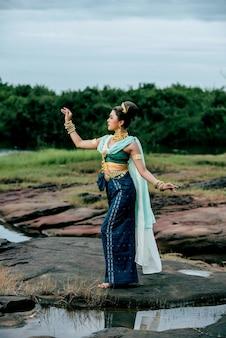 Ritratto di giovane bella donna che indossa in costume tradizionale con ornamento in posa nella natura in thailandia