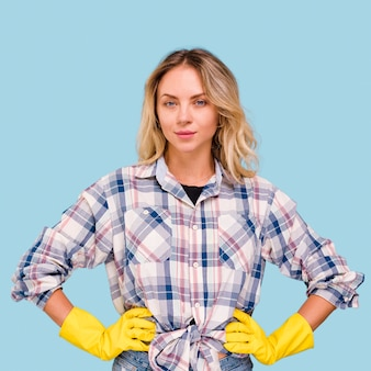 Portrait of young beautiful woman wearing yellow gloves looking at camera