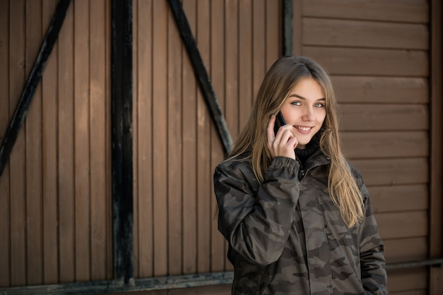 Portrait young beautiful woman in winter in the snow using mobile phone