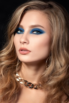 Portrait of young beautiful woman with blue smokey eyes fashion makeup.