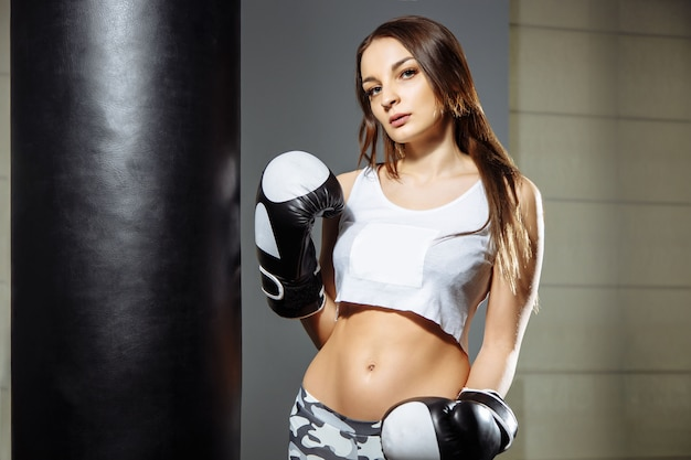Portrait of a young beautiful woman with boxing gloves in the gym.