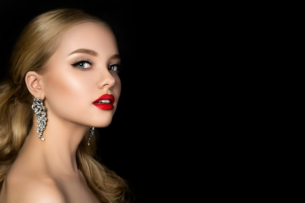 Portrait of young beautiful woman with evening make up over dark background