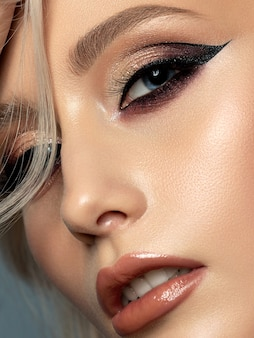 Portrait of young beautiful woman with evening make up. modern fashion eyeliner wing. closeup, partial face view