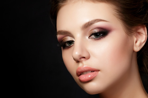 Portrait of young beautiful woman with evening make up posing over black background