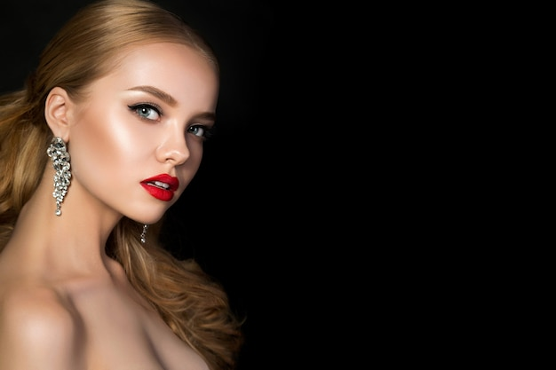Portrait of young beautiful woman with evening make up posing over dark background