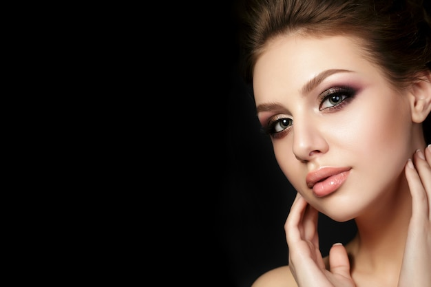 Portrait of young beautiful woman with evening make up touching her face over black background