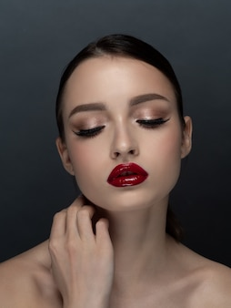 Portrait of young beautiful woman with evening make up touching her face. makeup