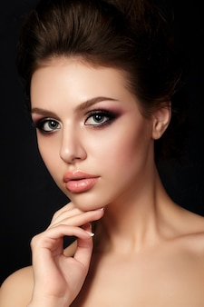 Portrait of young beautiful woman with evening make up touching her face. red and gold multicolored smokey eyes.