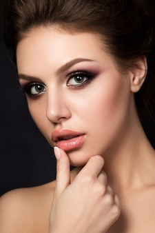 Portrait of young beautiful woman with evening make up touching her lips over black background